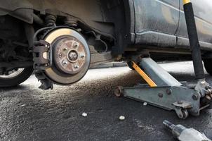 wiel van een auto vervangend, houdt krik het lichaam vast foto