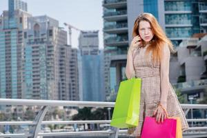 koopjes. jong meisje met boodschappentassen en kijken in de winkel foto