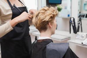 gelukkige kapper die het haar van klanten snijdt foto
