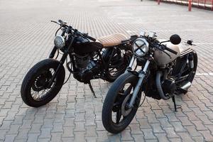 twee vintage motorfiets op parkeerplaats tijdens zonsondergang foto
