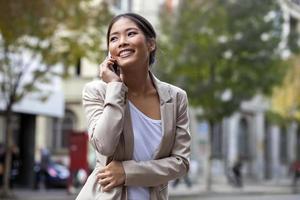 jonge vrouw en slimme telefoon lopen op straat foto