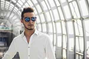 knappe jonge man in treinstation of luchthaven