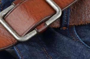 blauwe spijkerbroek met leren riem foto