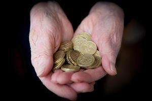 bejaarde handen met Britse pond munten foto