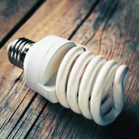 close up van energiebesparende lamp op houten bureau foto