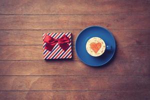 beker en geschenkdoos op houten achtergrond foto