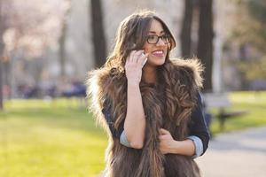 jonge vrouw in park praten op mobiele telefoon foto