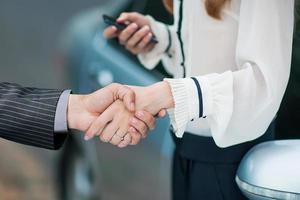 mannenhand autosleutel geven aan vrouwelijke hand. foto
