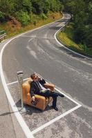 zakenman zittend op een stoel in het midden van de weg