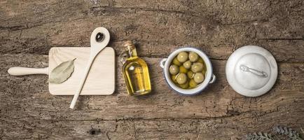 olijfolie en olijven houten tafel foto