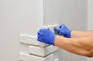 tegenover wand decoratieve tegels, arbeiders in blauwe handschoen foto