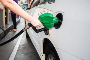 vrouwelijke hand met groene pomp benzine vullen