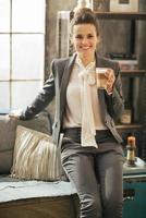 Glimlachende zakenvrouw met koffie latte zittend op divan foto