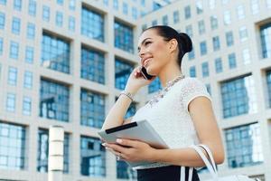 jonge zakenvrouw buiten op telefoon met digitale tablet in de hand foto