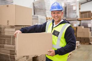 werknemer dragende doos in magazijn