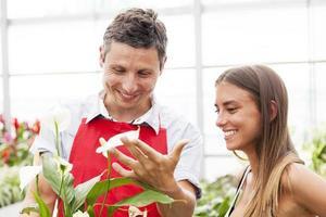 lachende verkoper verkoopt een plant aan een mooie klant foto