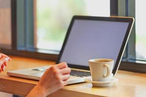 Azië mooi met behulp van haar laptop en koffie drinken in café foto