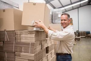 lachende magazijnmedewerker het nemen van een doos