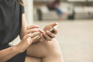 jonge vrouw met behulp van telefoon buiten in de stad foto