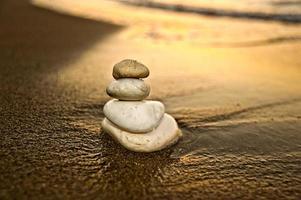 evenwichtige rotsen bij zonsondergang die teamwork voorstellen foto