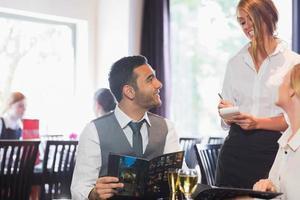 knappe zakenman eten bestellen bij serveerster foto