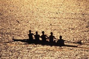 team van roeiers aftekenen bij zonsondergang foto