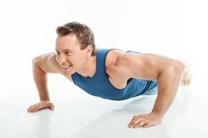 aantrekkelijke jonge gezonde sportman doet push-ups foto