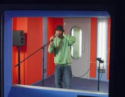 jonge man zingen in de studio foto