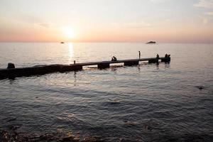 zonsondergang en silhouet mensen op pier foto