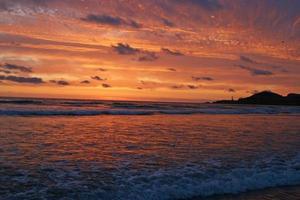 prachtige zonsondergang over de vuurtoren en de zee foto