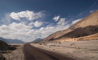 woestijnweg met horizon blauwe hemel en witte wolken foto