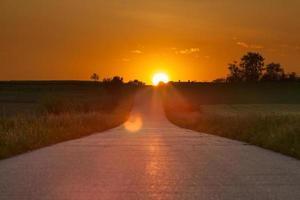 rijden op een asfaltweg richting de ondergaande zon