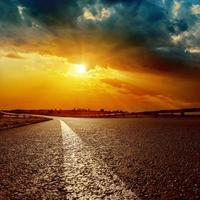 dramatische zonsondergang en asfaltweg naar horizon foto