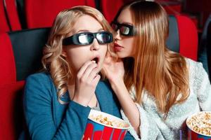 vrouw geheim delen in de bioscoop foto