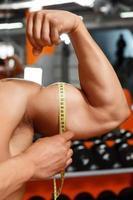 man meten van de grootte van zijn biceps foto