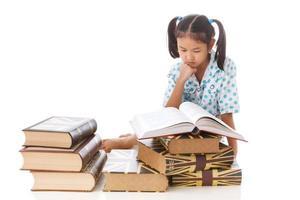Aziatisch leuk meisje dat een boek leest en op vloer zit. foto