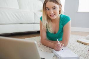 gelukkig blonde liggend op de vloer doet haar opdracht met behulp van laptop