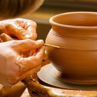 handen van een pottenbakker, waardoor een aarden pot ontstaat foto