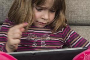 klein meisje en een digitale tablet foto