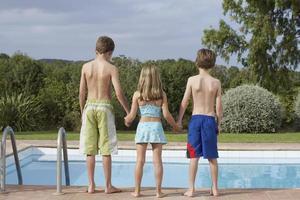 twee jongens en een meisje aan de rand van het zwembad foto