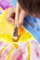 sluit omhoog van het penseel van de jongensholding om een zonsondergangscène te creëren foto