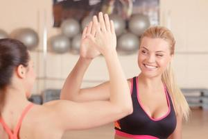 twee vriendinnen geven high five in de sportschool foto