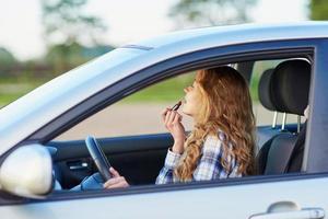 vrouw lippenstift toepassen in een auto tijdens het rijden foto