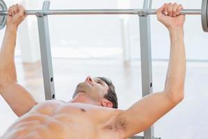shirtless fit man tillen de halterbankdrukken foto