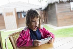 klein meisje met een smartphone foto
