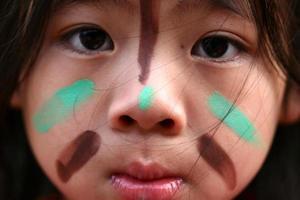gezicht van een Indiaans kind met geschilderde markeringen foto
