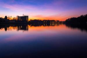 kleurrijke stadsgezicht 's nachts, na zonsondergang, langs de rivier, Oekraïne