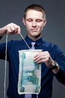 zakenman ontbinden de 1000-roebel als een gebreide stof foto