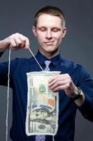 zakenman ontbinden het 100-bankbiljet als een gebreide stof