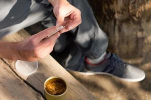 man rolt een cannabis joint foto